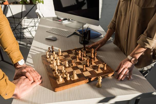 cropped shot of colleagues playing chess at workplace - Photo, Image