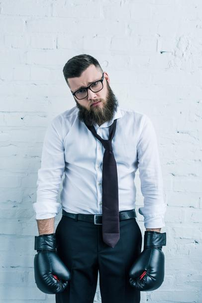 portrait of sad businessman in boxing gloves against white brick wall - Photo, Image