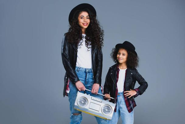 mother and daughter with retro boombox isolated on grey - Photo, Image
