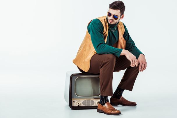 handsome retro styled man sitting on vintage television on white - Photo, Image