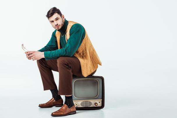 handsome retro styled man sitting on vintage television and looking at camera on white - Photo, Image