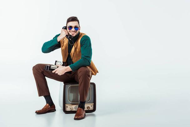 smiling retro styled man sitting on vintage television and talking by stationary telephone  - Photo, Image