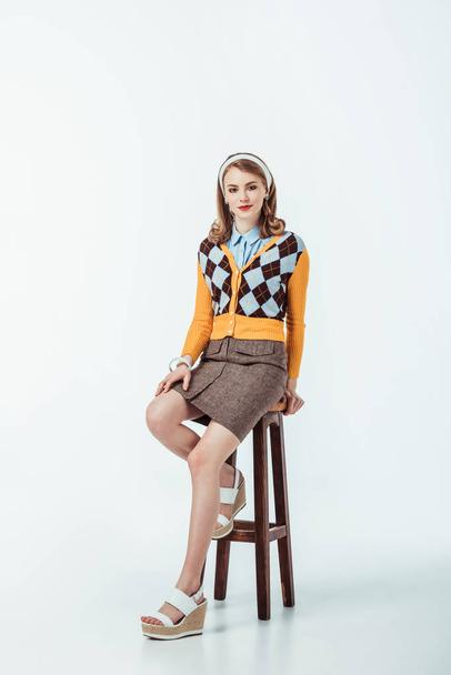 attractive retro styled girl sitting on wooden chair and looking at camera on white - Photo, Image