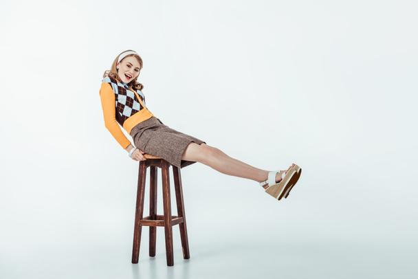 smiling beautiful retro styled girl sitting on wooden chair and looking at camera on white - Photo, Image
