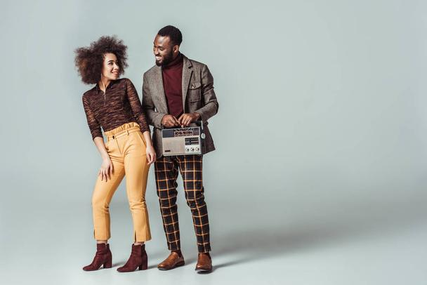 happy african american retro styled couple looking at each other with vintage radio on grey - Photo, Image