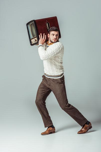 retro styled handsome man running away with vintage television on shoulder - Photo, Image