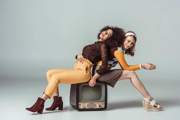 happy multicultural retro styled girls posing on vintage television on grey - Photo, Image