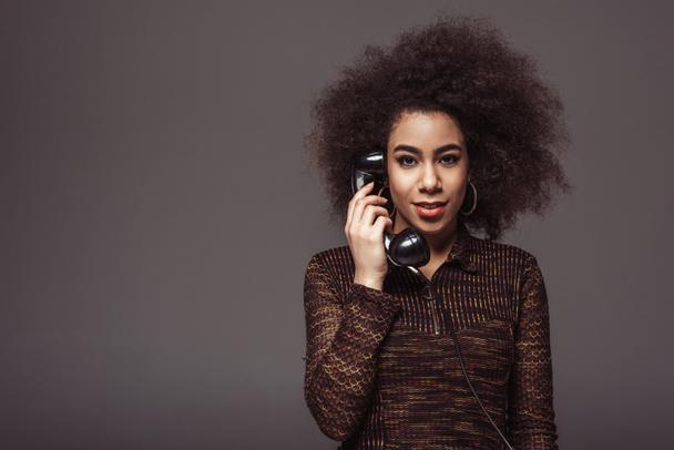 african american retro styled girl talking by vintage stationary telephone isolated on grey - Photo, Image