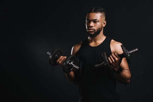 young african american sportsman exercising with dumbbells and looking away isolated on black - Photo, Image
