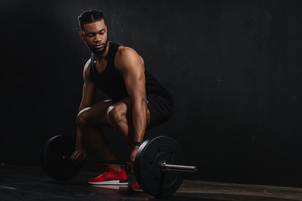 full length view of young african american sportsman lifting barbell on black  - Photo, Image
