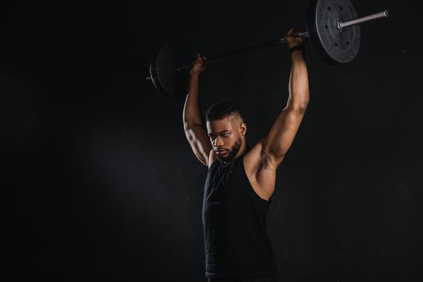 muscular young african american sportsman lifting barbell and looking away isolated on black - Photo, Image