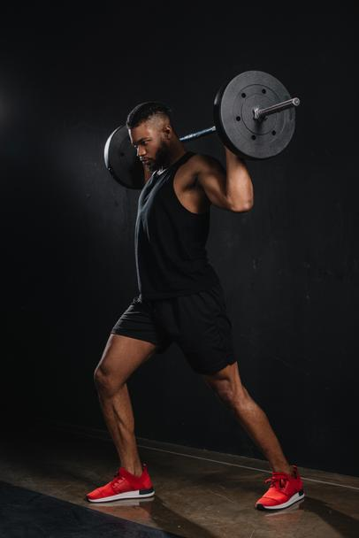 muscular young african american sportsman lifting barbell on black  - Photo, Image