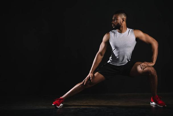 athletic young african american man in sportswear exercising and looking away on black - Photo, Image