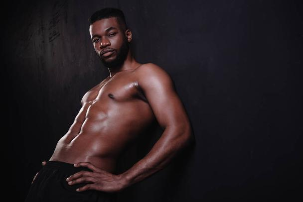 handsome shirtless muscular african american man looking at camera on black  - Photo, Image