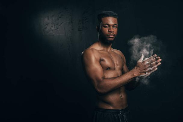 shirtless young african american sportsman applying talcum to hands and looking at camera on black  - Photo, Image
