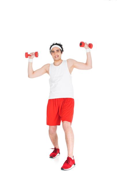 Young thin man in sportswear with dumbbels in hands isolated on white - Photo, Image