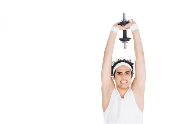 Young skinny man holding dumbbell over own head - Photo, Image