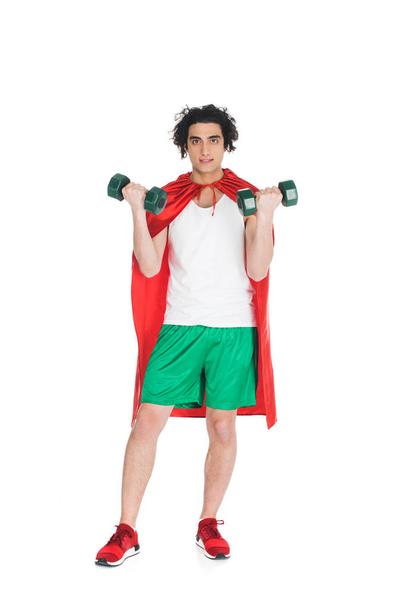 Thin sportsman with dumbbells in hands and wearing red cape isolated on white - Photo, Image