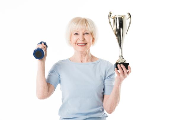 Senior sportswoman with trophy and dumbbell isolated on white - Photo, Image