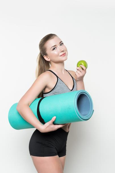 Smiling fitness woman holding apple and yoga mat isolated on white - Photo, Image