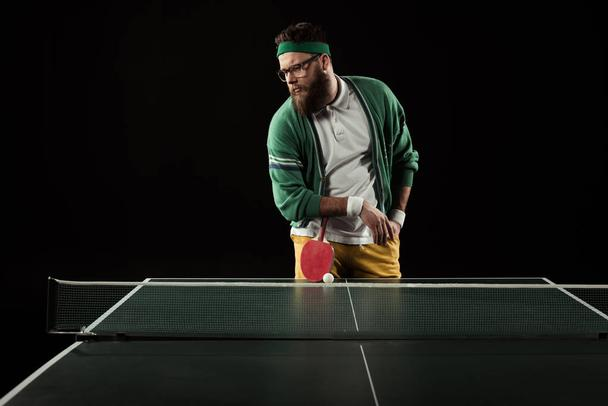 bearded tennis player leaning on racket on tennis table isolated on black - Photo, Image