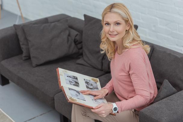sorrindo mulher madura com álbum de fotos descansando no sofá em casa  - Foto, Imagem