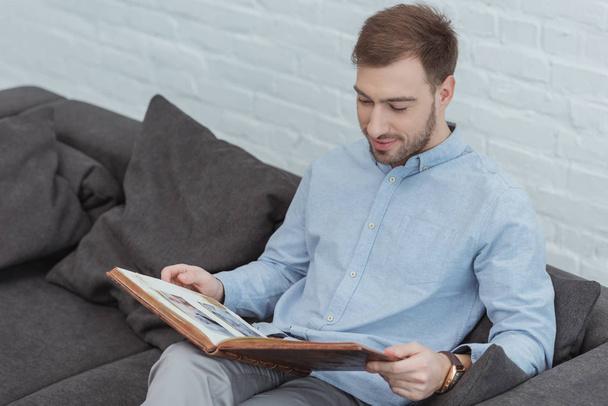 retrato de homem olhando para fotos no álbum de fotos enquanto descansa no sofá em casa  - Foto, Imagem