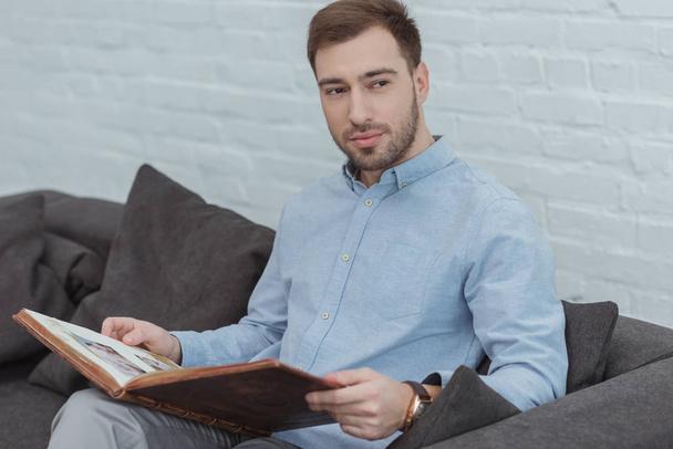 retrato de homem pensativo com álbum de fotos descansando no sofá em casa  - Foto, Imagem