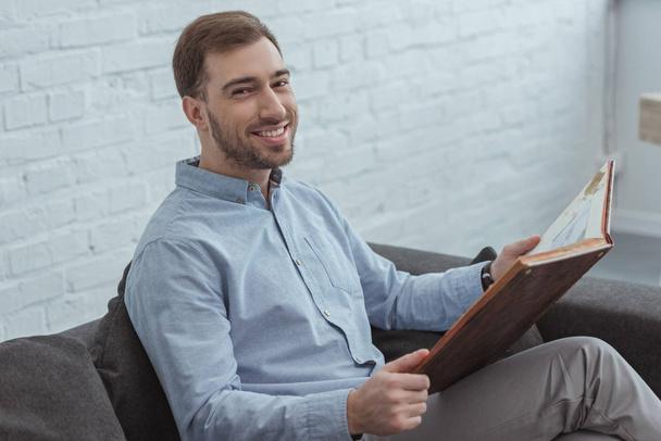 retrato de homem sorridente com álbum de fotos descansando no sofá em casa  - Foto, Imagem