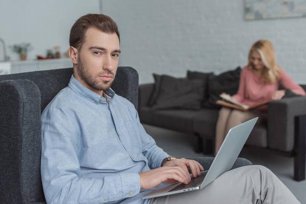foco seletivo do homem com laptop e mãe olhando para fotos no álbum de fotos no sofá em casa  - Foto, Imagem