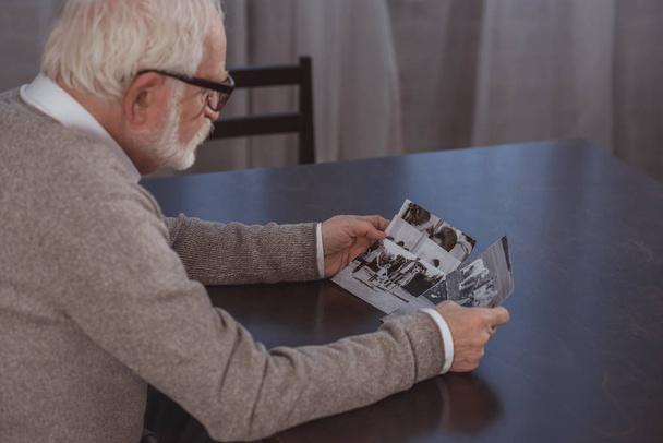 Seitenansicht eines Mannes mit grauen Haaren, der am Tisch sitzt und sich zu Hause Fotos ansieht - Foto, Bild