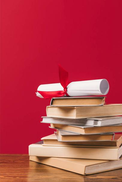 Diploma on top of stack of books on red - Photo, Image