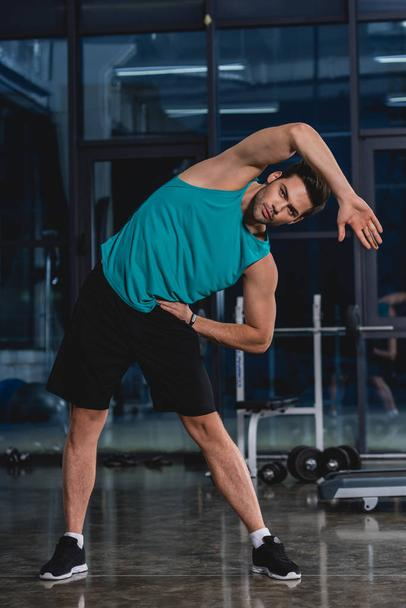 athletic man stretching in sports hall - Photo, Image