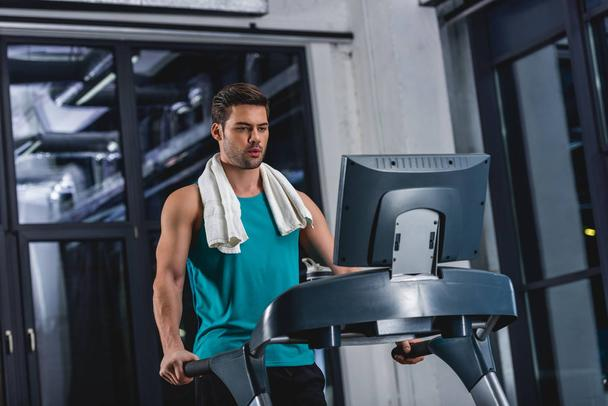 tired sportsman with towel exercising on treadmill in sports center - Photo, Image