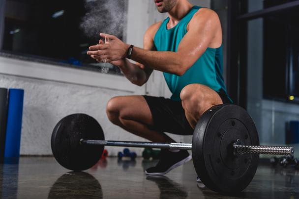 cropped view of sportsman with talcum powder training with barbell in gym - Photo, Image
