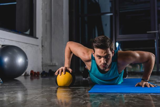 sportsman doing push ups with medicine ball on yoga mat in gym - Photo, Image