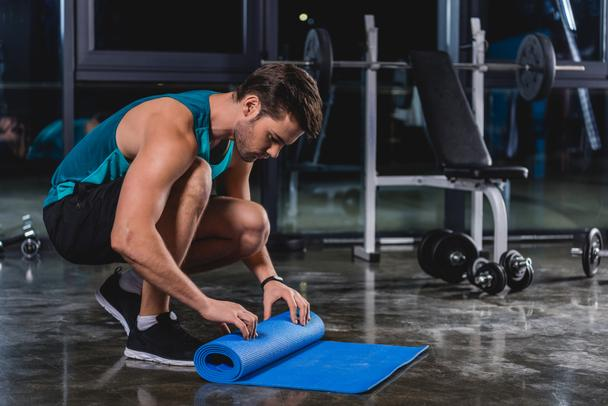 sportsman rolling up yoga mat in sports center - Photo, Image