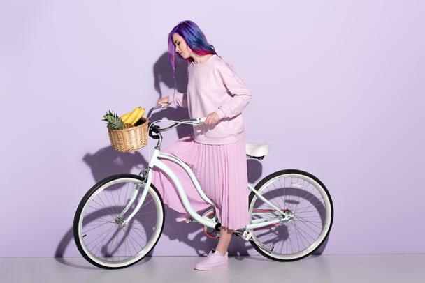 attractive young woman in pink clothing on bicycle with pineapple and bananas in basket - Photo, Image