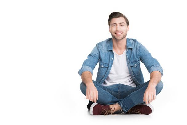 young smiling man sitting in jeans looking at camera, isolated on white - Photo, Image