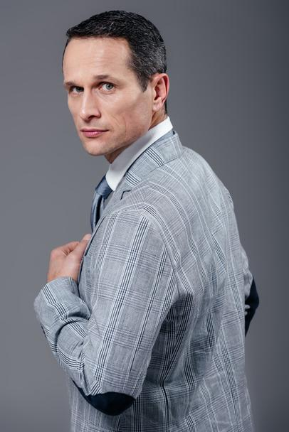 handsome adult businessman in stylish suit turning back and looking at camera isolated on grey - Photo, Image