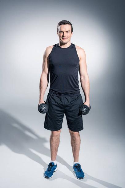 Active man exercising with dumbbells on grey background - Photo, Image