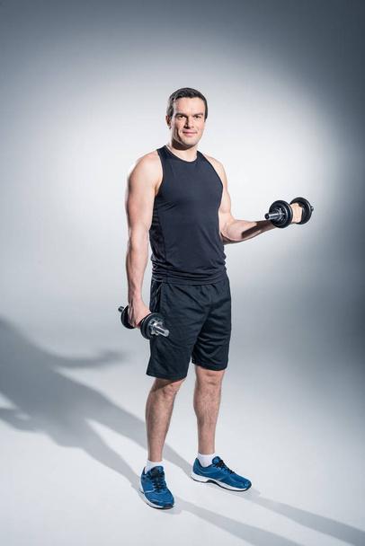 Young man athlete exercising with dumbbells on grey background - Photo, Image
