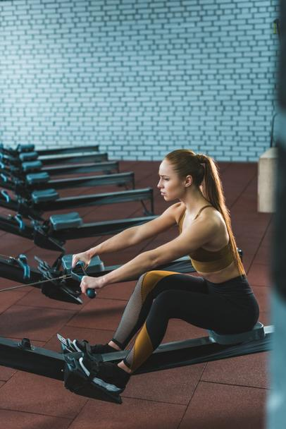 Side view of sportswoman doing exercise on rowing machine in sports center - Photo, Image