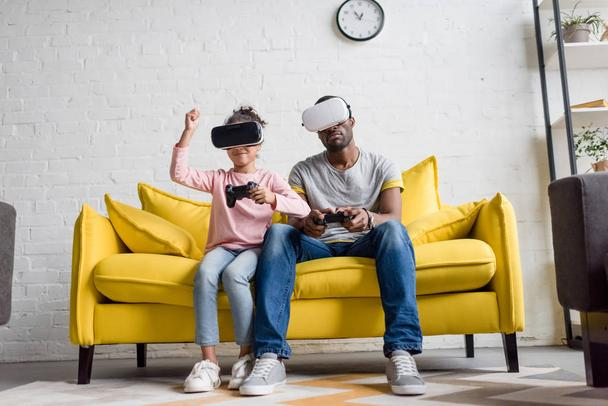 young father and daughter in vr headsets playing video games on couch at home - Photo, Image
