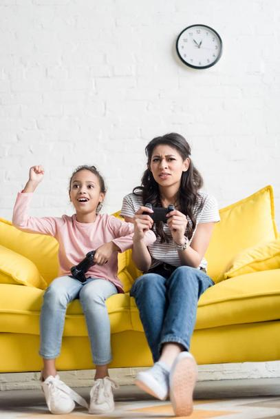 emotional mother and daughter playing video games at home on couch - Photo, Image