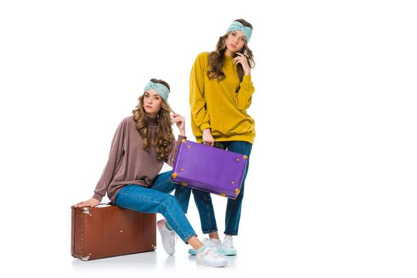 attractive retro styled twins with travel suitcases isolated on white - Photo, Image