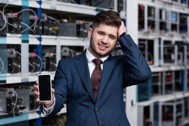 failed young businessman showing smartphone at cryptocurrency mining farm - Photo, Image