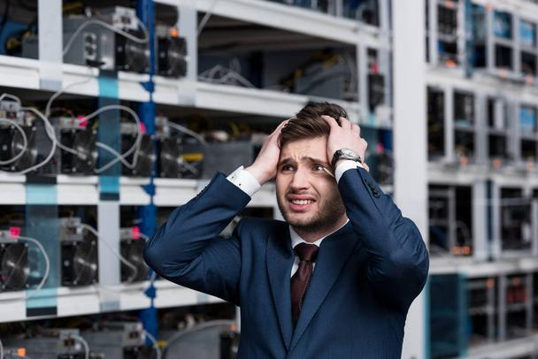 failed young businessman holding head at cryptocurrency mining farm - Photo, Image