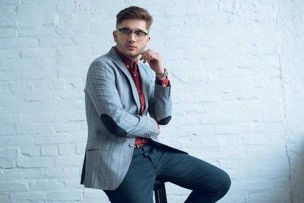 Bearded young man wearing stylish suit sitting in front of white wall - Photo, Image