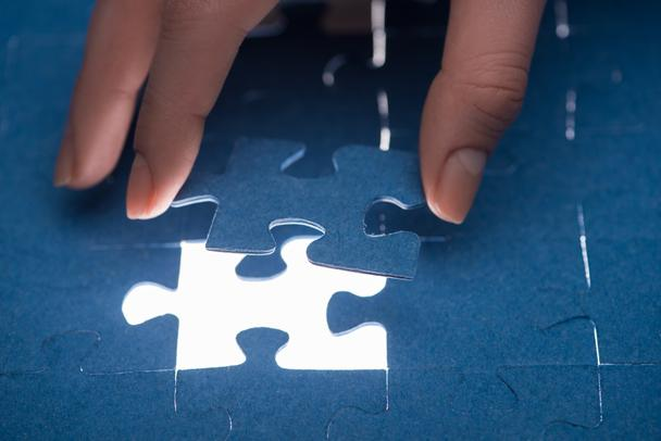 cropped image of businesswoman inserting last missing puzzle, business concept - Photo, Image